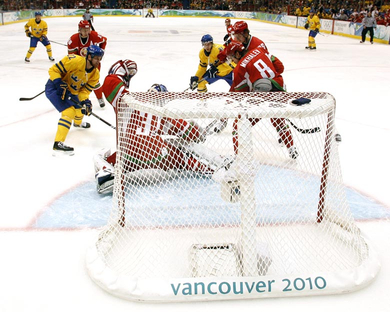 Vancouver Canuck DANIEL SEDIN (22, left) shoots the puck into the right hand corner of Belarus netminder ANDREI MEZIN's goal to send Sweden in front 1-0 at the 2010 Winter Olympic Games in Vancouver, Canada. (Jukka Rautio/HHOF-IIHF Images)