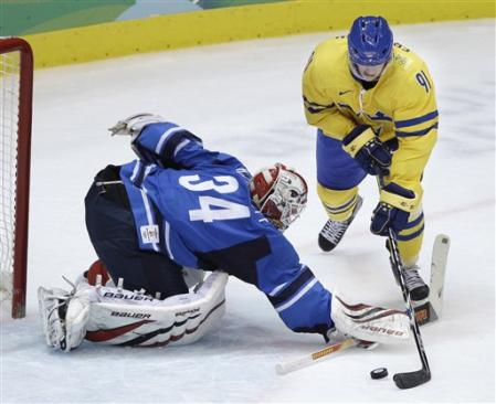 Sweden's LOUI ERIKSSON (91) sweeps around Finland goalkeeper MIIKKA KIPRUSOFF (34) to score his second and the team's third goal of the match between rival Scandanavian powers at the 2010 Winter Olympics in Vancouver. (AP Photo)