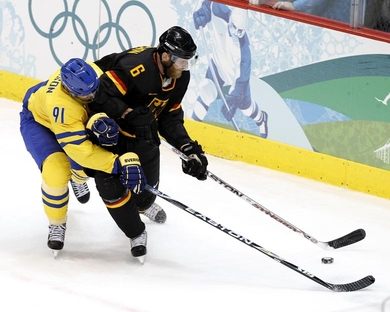 German defenseman SVEN BUTENSCHON (6) uses his body to shield Swedish goal-scorer LOUI ERIKSSON (91) at the 2010 Winter Games in Vancouver, Canada. Butenschon, a veteran of 140 National Hockey League games, last played in the NHL for the Vancouver Canucks four years ago. Eriksson scored the second goal in Sweden's 2-0 defeat of Germany in Group C at the Olympics. (Jukka Rautio/HHOF-IIHF Images)