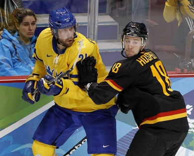 Two-time Olympic gold medalist PETER FORSBERG (21), participating at his fourth Winter Games for Sweden, is marked by Germany's KAI HOSPELT (18) in Vancouver. (Jukka Rautio/HHOF-IIHF Images)