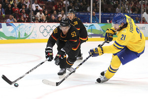 PETER FORSBERG (21) snaps off a shot for Sweden as German defender ALEXANDER SULZER (52) of the Nashville Predators tries to intercede. It was Sulzer's giveaway in his own defensive corner that directly led to Sweden's second goal in Germany's 2-0 loss at the 2010 Vancouver Games. (Jukka Rautio/HHOF-IIHF Images)