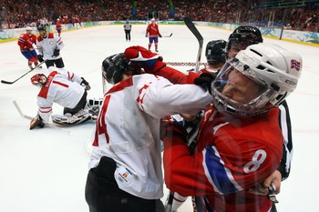 Switzerland's ROMAN WICK (14) lands an elbow to the shielded face of Norway's MADS HANSEN (8) in Vancouver. Hansen's second period power play goal handed Norway a 2-1 lead. (Bruce Bennett/Getty Images)