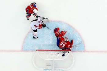 Swiss forward ROMANO LEMM (67), tracked by Norwegian defender TOMMY JAKOBSEN (7), receives Sandy Jeannin's creative pass in the crease. (Bruce Bennett/Getty Images)
