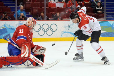 Switzerland's RAFFAELE SANNITZ (39) in the process of scoring one of, if not the most, skillful goal of the 2010 Winter Olympic Games against Norway's goaltender, PAL GROTNES. (Matthew Manor/HHOF-IIHF Images)