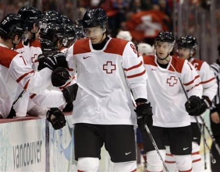 JULIEN SPRUNGER (86) bumps fists with his teammates at the bench following the 2004 Minnesota Wild draft pick's opening goal against Norway at the 2010 Winter Games in Vancouver. (Julie Jacobson/AP)