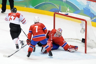 Switzerland forward ROMANO LEMM (67) skates off after scoring the winning goal in overtime as defenseman TOMMY JAKOBSEN (7) sees the Norwegians' best effort at the 2010 Vancouver Games go unrewarded. (Matthew Manor/HHOF-IIHF Images)