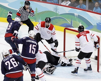 United States forward ZACH PARISE (9) pops the puck past prone Swiss goalie JONAS HILLER into the net to break a third-period scoreless tie in the quarterfinals at the 2010 Winter Olympics in Vancouver. Looking on are Swiss forward THIERRY PATERLINI (23) and captain MARK STREIT (7) as well as United States attackers JAMIE LANGENBRUNNER (15) ane PAUL STASTNY (26). (Jukka Rautio/HHOF-IIHF Images)