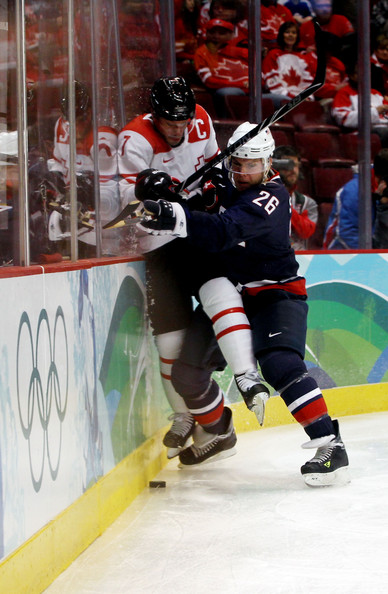 United States forward PAUL STASTNY (26) of the Colorado Avalanche slams Switzerland defenseman and captain MARK STREIT of the New York Islanders into the boards at the Vancouver Games. (Bruce Bennett/Getty Images)