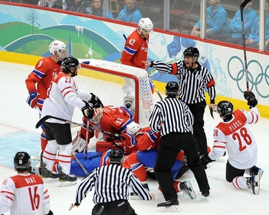 Penalty Shot! The referee points to the center ice face-off dot and awards Switzerland a penalty shot as Norwegian defenseman JONAS HOLOS is correctly judged to have intentionally covered the puck in the goal crease. (Matthew Manor/HHOF-IIHF Images)