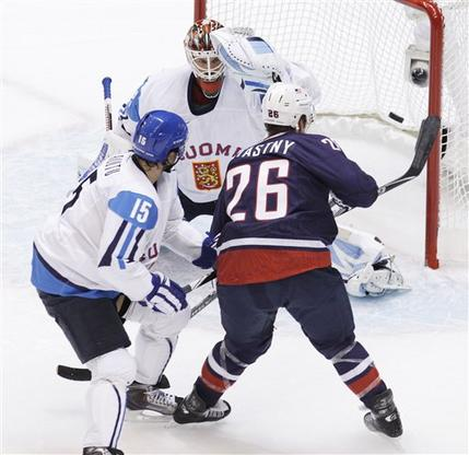 United States forward PETER STASTNY (26) beats Finland goaltender NIKLAS BACKSTROM to the glove side while being hooked by Finnish forward TUOMO RUUTU (15) of the Carolina Hurricanes in the semifinals at the 2010 Winter Olympics from Vancouver. (Chris O'Meara/AP)