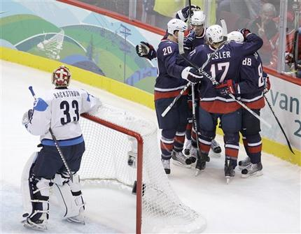 United States skaters RYAN SUTER (20), DUSTIN BROWN (32) and RYAN KESLER (17) circle around the goal-scorer Kane behind Backstrom and the Finland net in Vancouver. (Chris O'Meara/AP)