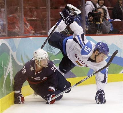 United States defenseman BRIAN RAFALSKI (28) flips Finnish forward VALTTERI FIPPULA (51) in pursuit of the puck at the Olympic semifinals in Vancouver. Both Filippula and Rafalski skate professionally for the Detroit Red Wings in the National Hockey League. (Matt Slocum/AP)