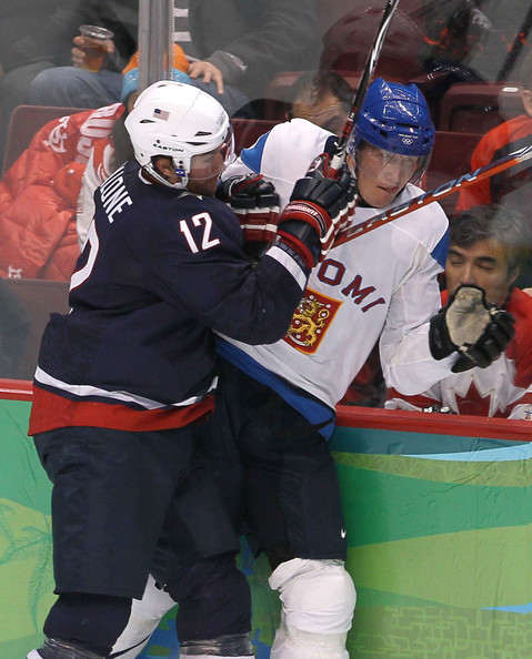 The Finnish defenseman Pitkanen receives an Olympic-sized stick upside the head from United States forward RYAN MALONE (12) along the boards in Vancouver. (Bruce Bennett/Getty Images)