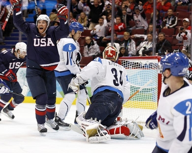 United States forward RYAN MALONE (12) is jubilant just after the third American goal inside the first ten minutes of the semifinal match at the 2010 Winter Olympics in Vancouver. Malone had opened the scoring after an egregious error by Finland netminder MIIKKA KIPRUSOFF just two minutes in. Here, Kiprusoff (34) and Finnish defenseman SAMI SALO look back at the puck in the net at Canada Hockey Place. (Jeff Vinnick/HHOF-IIHF Images)