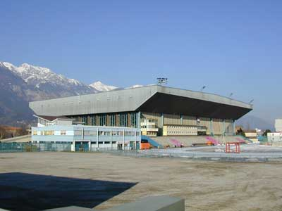 The OLYMPIAHALLE in the Austrian city of Innsbruck is the only arena in the world to have ever hosted two ice hockey tournaments at the Winter Olympic Games. In the background of the photo would be the Tyrolean Alps.