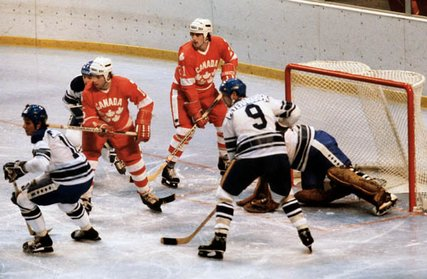 Forwards JOHN DEVANEY (15, left) and KEVIN PRIMEAU (21, right) park in front of Holland's goal during Canada's 10-1 romp of the Dutch on the opening day of Red Group play at the 1980 Winter Olympics. Both Devaney and Primeau registered a goal for Canada in the match.