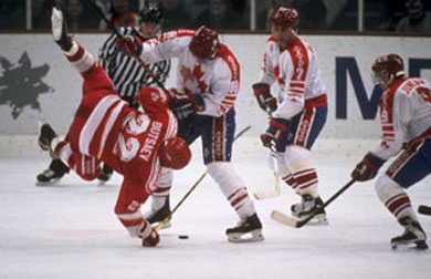 Canada's ERIC LINDROS (88) upends VYACHESLAV BUTSAYEV (22) of the Unified Team at the 1992 Winter Olympic Games in Albertville, France. The fall of the Berlin Wall in November of 1989 touched off a series of events that resulted in great upheaval for the world of international hockey that contiuned well into the 1990s.