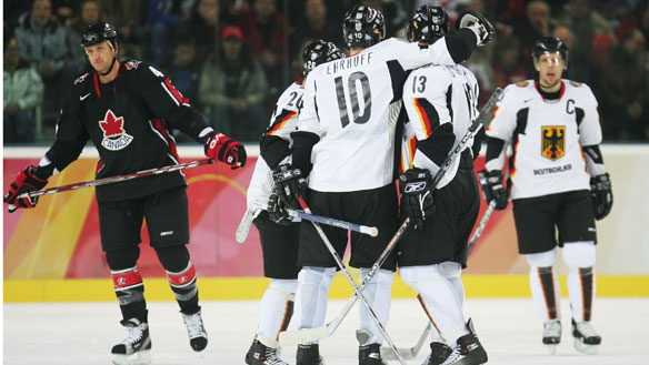 German defenseman CHRISTIAN EHRHOFF, then a San Jose Shark, is congratulated by CHRISTOPH SCHUBERT (13) and DANIEL KREUTZER (26) as captain STEFAN USTDORF (16) skates over at the 2006 Winter Olympic Games in Turin, Italy. Ehrhoff has just scored to cut the Canadian lead to 3-1 in the second period. Canada will eventually defeat Germany 5-1 in the Group B round-robin match. (Robert Laberge/Getty Images)