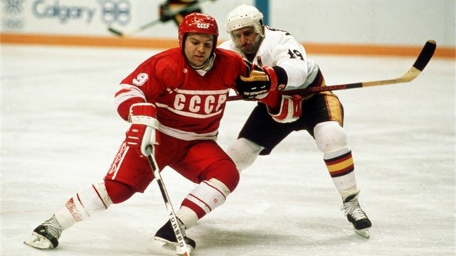 Soviet left wing VLADIMIR KRUTOV (9) fends off a West German check at the 1988 Winter Games. The USSR defeated West Germany 6-3 in Calgary. Krutov finished the Olympic tournament top scorer with 15 points (6 go 9 as) in eight games.