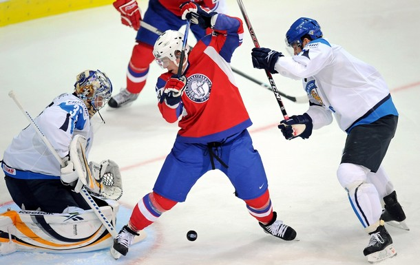 Norway's PER AGE SKRODER jousts with Finnish defenseman TOPI JAAKOLA in front of goaltender PEKKA RINNE at the 2009 IIHF World Championships in Zurich. Skroder was injured in Norway's Olympic opener versus Canada and is out of the 2010 Winter Games at Vancouver.