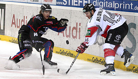 ERC Ingolstadt's American defenseman TIM HAMBLY (#14, dark shirt) and Koelner Haie's Swedish forward DANIEL RUDSLATT (#14, white shirt) haggle for possession of the puck behind the net at Saturn Arena in Bavaria. ERC Ingolstadt elminated Koelner Haie two games to one and advance to the quarterfinals of the Deutsche Eishockey Liga playoffs. (Stefan Jonat/Eishockey.Info)