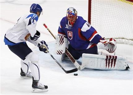 The Finn Jokinen (12) heads for the five-hole of Halak guarding the Slovakian goal at Canada Hockey Place. (Gene J. Puskar/AP)