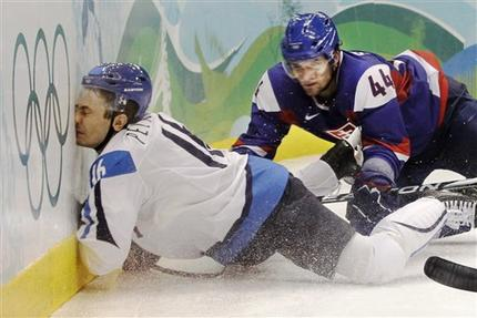 Finland forward VILLE PELTONEN (16) punishes the muraled board with his face as Slovakia defenseman ANDREJ SEKERA (44) observes in the Bronze Medal Match at the 2010 Winter Olympics from Vancouver. Perhaps Peltonen was not impressed with the artwork on display and chose to protest in an unusual fashion. (Julie Jacobson/AP)