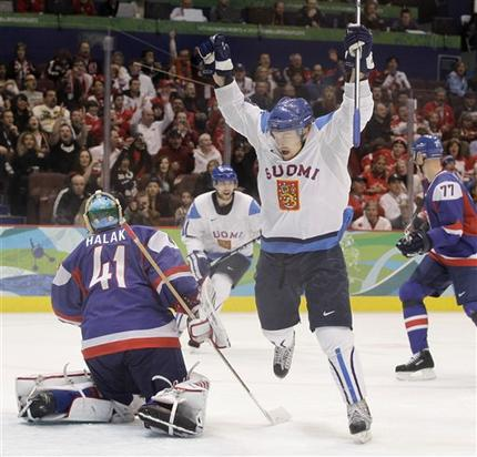 Finnish forward NIKLAS HAGMAN holds his stick high in front of Slovak goaltender JAROSLAV HALAK after the not-pictured SAMI SALO opened the scoring in the Bronze Medal Match at Canada Hockey Place. (Julie Jacobson/AP)