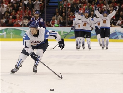 In the waning seconds of the Bronze Medal Match, Finland forward VALTTERI FILPPULA (51) chases down the puck for the clinching empty-net goal as his teammates down ice begin victory celebrations at the Winter Olympics in Vancouver. (Julie Jacobson/AP)
