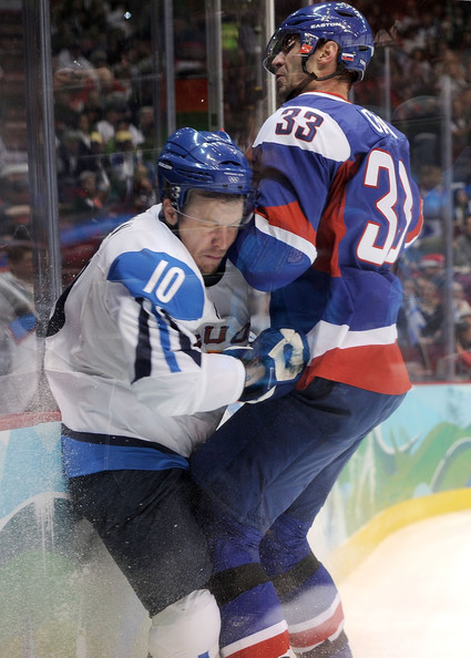 Finland's top scorer at the 2010 Winter Olympics, Calgary Flames forward NIKLAS HAGMAN (10), is crunched against the boards by Slovakia defenseman ZDENO CHARA (33) of the Boston Bruins in the Bronze Medal Match from Vancouver. (Harry How/Getty Images)