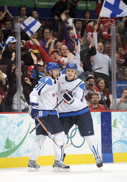 With Finnish supporters showing the flag in the background, MIKKO KOIVU (9) and SAMI SALO (6) celebrate the opening goal of the Bronze Medal Match at the 2010 Winter Olympics. Koivu had created the chance with hustle in the offensive zone. Salo, meanwhile, picked a fine time to pot his first goal of the Vancouver Games. (Harry How/Getty Images)
