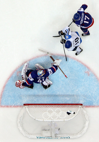 The hook of the Edmonton Oilers defenseman is in vain as the Montreal Canadiens netminder waves his goalstick with futility; the Calgary Flames forward has already lit the fuse for Finland's comeback in the Bronze Medal Match at Vancouver. (Bruce Bennett/Getty Images)