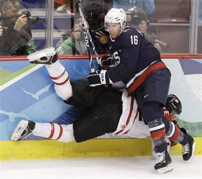Another angle of the American Pavelski (16) pounding the Canadian Boyle (22) into the boards in the Gold Medal Game of the 2010 Winter Olympics in Vancouver. (Julie Jacobson/AP)