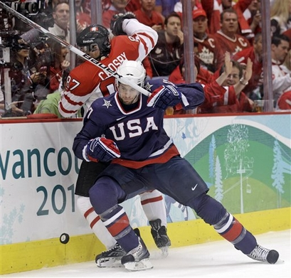 United States forward RYAN KESLER (17) of the Olympic host city's Vancouver Canucks checks the host nation's star player, SIDNEY CROSBY (87) of the Stanley Cup champion Pittsburgh Penquins, into the boards in a bid for the puck at Canada Hockey Place. Both players would register their names on the scoresheet of the Gold Medal Game at the 2010 Vancouver Winter Olympics. (Matt Slocum/AP) 