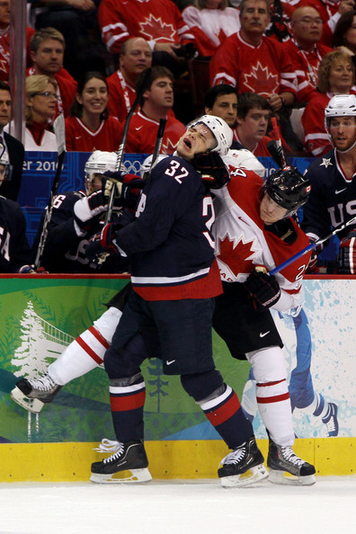 Canada's COREY PERRY (24) of the Anaheim Ducks deals a knock on the back of the neck for United States forward DUSTIN BROWN (32) of the Los Angeles Kings right in front of the American bench during the Gold Medal Game of the Vancouver Games. (Bruce Bennett/Getty Images)