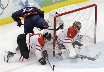 The United States quite literally came closest to scoring first --- Canada goaltender ROBERTO LUONGO starts the close shave with the save from American forward DUSTIN BROWN (32), who is dumped by his sliding NHL squadmate, defenseman DREW DOUGHTY (8) of the Los Angeles Kings in the Gold Medal Game at the Vancouver Olympics. (Chris O'Meara/AP)
