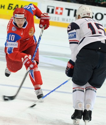 Russia's SERGEI MOZYAKIN (10) unleashes a slapshot as United States defenseman JOHN MICHAEL LILES (15) steadies himself in the semfinal match at the 2009 IIHF World Championships from Bern, Switzerland. (Alexander Nemenov/AFP/Getty Images)