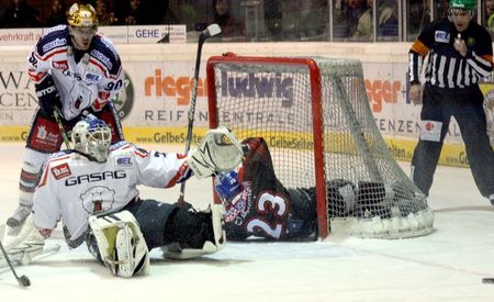 Eisbaeren Berlin goalie ROB ZEPP keeps his eye on the puck as Augsburg Panther forward MATT RYAN (23) literally crashes the net in DEL playoff action from the Curt Frenzel Stadion in Bavaria. Also on hand is CONSTANTIN BRAUN (90) for Eisbaeren Berlin. (eishockey-magazin.de photo) 