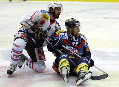 EHC Kloten's Finnish international KIMMO RINTANEN (33) has a seat on the ice at the Kolping Arena with SC Bern's Swiss Olympic defender PHILIPPE FURRER (29) right behind in the Nationalliga A semifinals. SC Bern set EHC Kloten down four straight games and storms into the final round unbeaten in eight playoff games. SC Bern last won Switzerland's elite league championship in 2004. (Keystone photo)