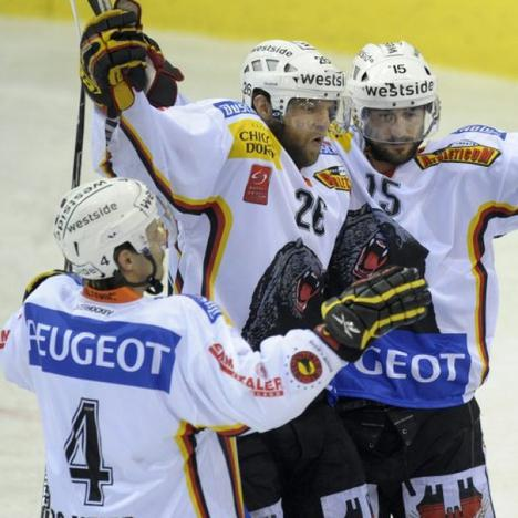 Swiss Olympic forward MARTIN PLUESS (26) signals Game Four's first goal for SC Bern with defenseman DOMINIC MEIER (4) and Canadian legionnaire BRETT MCLEAN (15) in the Nationlliga A championship finals at Les Vernets in Geneva. (Keystone photo)