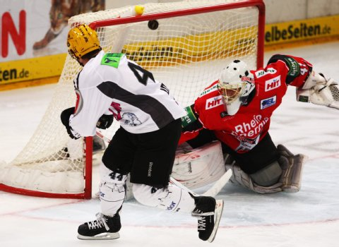Frankfurt Lions forward JEFF ULMER (44) lifts the puck over Koelner Haie's Swiss goalkeeper LARS WEIBEL in Deutsche Eishockey Liga action from the Lanxess Arena in Cologne. (Getty Images photo)