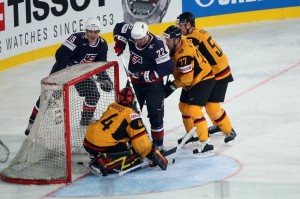 United States forward RYAN CARTER (22) muscles the puck past German goaltender DENNIS ENDRAS in the third period of the preliminary round Group D match at the Veltins-Arena. (Christof Koepsel/Bongarts/Getty Images)